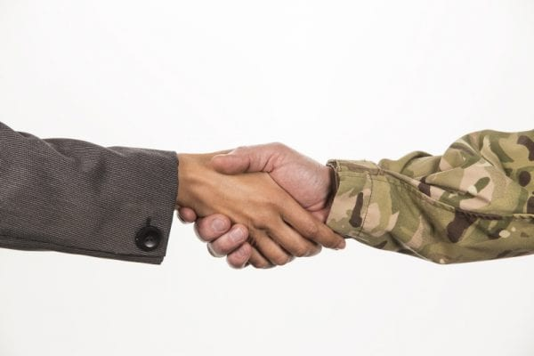 Female civilian and male serviceman shaking hands.